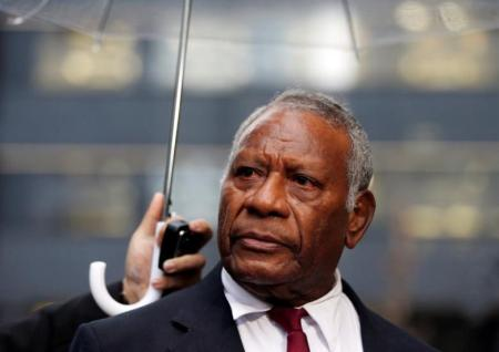 Vanuatu's President Baldwin Lonsdale, standing under an umbrella, listens to a question during an interview with Reuters, after attending the third United Nations World Conference on Disaster Risk Reduction (WCDRR), in Tokyo, March 16, 2015, before leaving to return home. REUTERS/Issei Kato