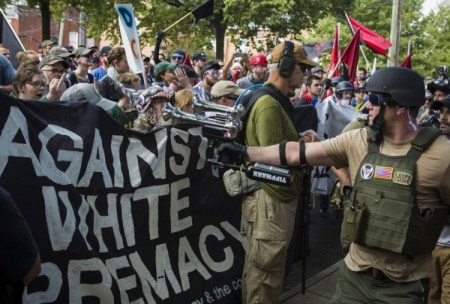 A participant in the Unite the Right rally blares a horn at protesters Aug. 12 in Charlottesville (Calla Kessler/The Washington Post)