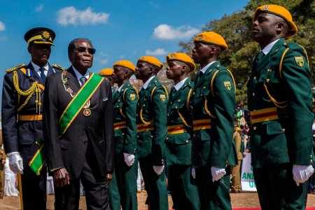 President Robert Mugabe inspecting an honor guard at a Heroes Day event held at National Heroes Acre in Zimbabwe in August. (Credit: Jekesai Njikizana/Agence France-Presse — Getty Images)