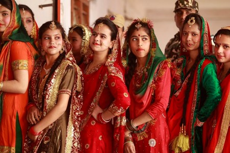 Indian girls dressed in traditional attire watch a cultural performance as they celebrate Lohri festival in Jammu, India, Saturday, Jan. 13, 2018. Lohri is a celebration of the winter solstice observed by Hindus and Sikhs in northern India. (AP Photo/Channi Anand)