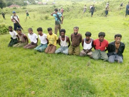 Ten Rohingya Muslim men with their hands bound kneel as members of the Myanmar security forces stand guard in Inn Din village September 2, 2017. Picture taken September 2, 2017. Handout via REUTERS