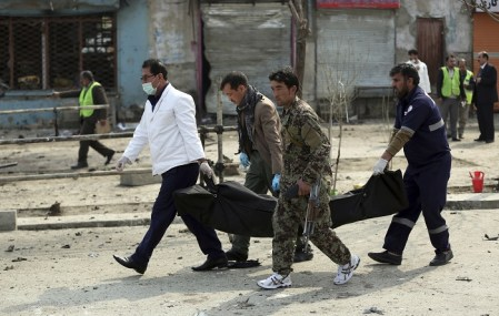 Security personnel carry a body at the site of a suicide attack in Kabul on March 9. (Massoud Hossaini/AP)