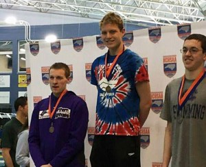 Sophomore Jake Johnson receives the first place award for the 100-yard backstroke at the North Carolina 3A Swimming finals. Johnson also received a third place award in the 200-yard freestyle and broke school records in both events. Photo taken from the Piranhas Facebook page.