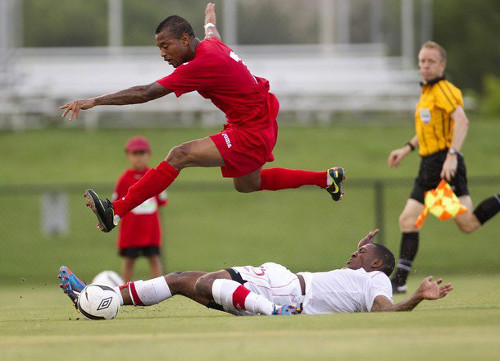 Photo: Trinidad and Tobago winger Lester Peltier hurdles a Canadian opponent during a friendly international in 2012.  (Courtesy AP)