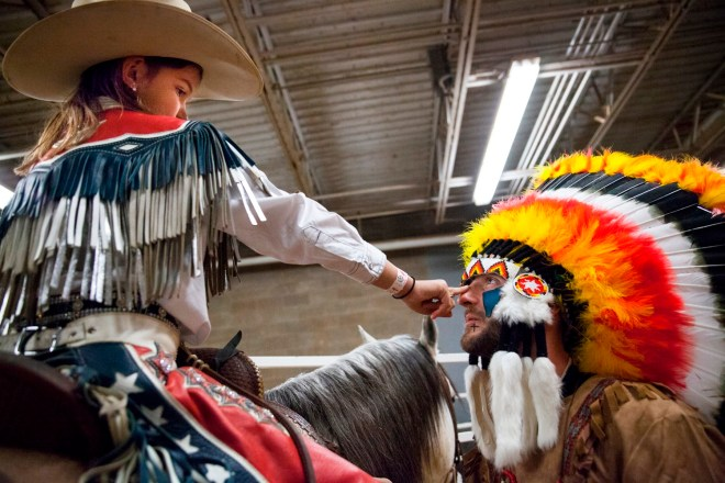 Oralee Madison, 8, checks bull fighter Chris Russell's face paint before the start of the Lone Star Championship Rodeo at the L.D Brown Agricultural Exposition Center in Bowling Green, Kentucky on Sunday, February 14th, 2016.|Skyler Ballard