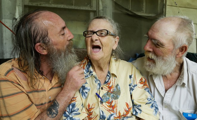 James Copas, 52 (left) and Harold Copas, 62 (right) sit on the front porch with their mother Mildred Walker, 89 as they enjoy the summer breeze and making their mother laugh. 23rd June 2016. Tompkinsville, Ky.