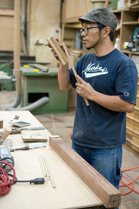 木製収納棚TANA食器棚のガラス戸取っ手を製作中の直井君