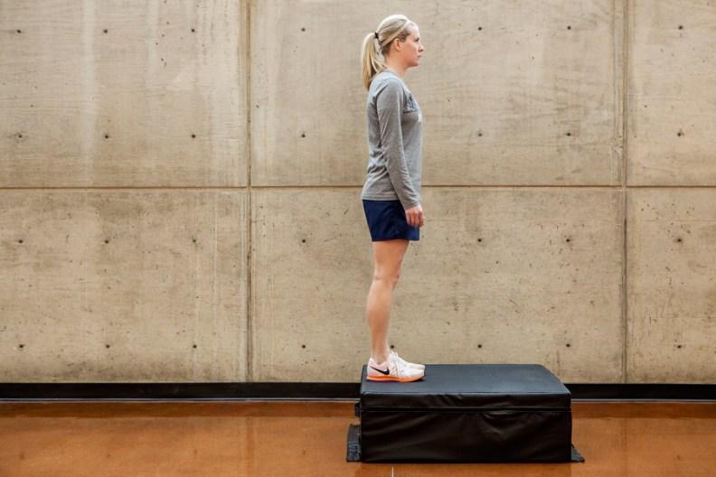 Leslie stands upright on step