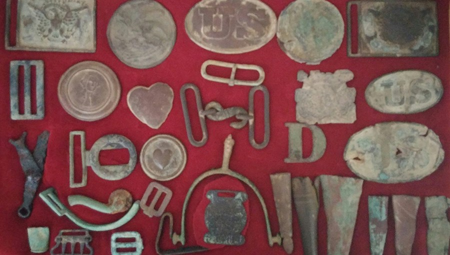 antique coins, medals, buckles, stirriups in a display case
