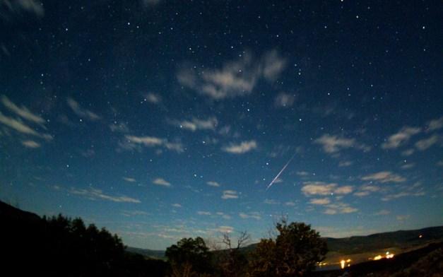 A perseid meteor streaks across a star-encrusted and cloud-scattered sky. Image Credit: Jimmy Westlake