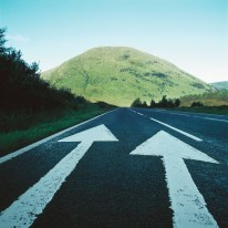 Two painted arrows on a road pointing towards a grassy mountain