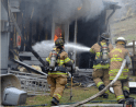 Firefighters attacking a structure fire