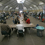 Homeless veterans fill a long line of tables receiving their nightly meal at a shelter in San Diego. Lenny Ignelzi/AP