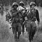 U.S. cavalrymen carry a fellow soldier to an evacuation zone after he was seriously wounded in South Vietnam. Peter Arnett/AP