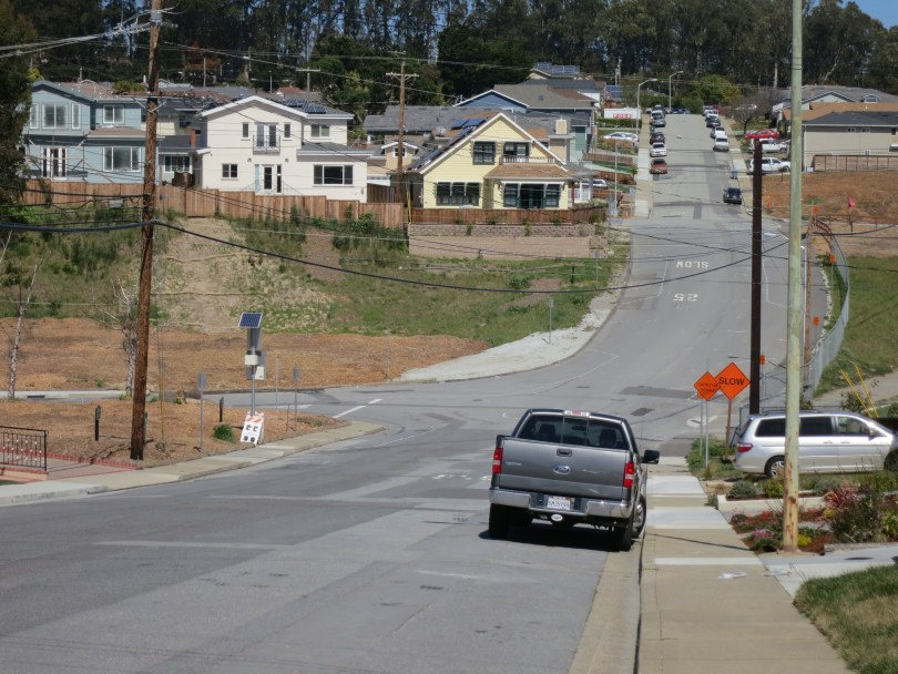 A view down Glenview Drive in San Bruno where homes once stood and empty lots remain. (Francesa Segre/KQED)