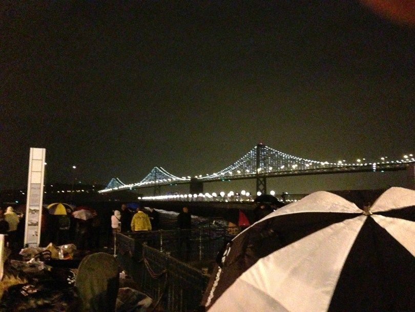 Umbrellas sprouted in the crowd watching as the bridge lit up. (Cy Musiker/KQED)