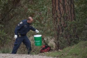 A California Highway Patarol officer receives Warbler's food bucket. (Deborah Svoboda/KQED)