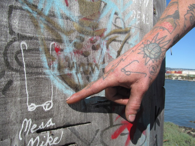 """Mike Brodie shows one of his tags at the 5th Avenue Marina in Oakland. He says he sometimes goes by """"Mesa Mike,"""" because he was born in Mesa, Arizona."""