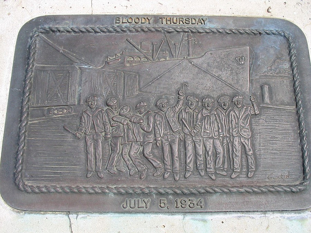 """Plaque accompanying the sculpture at the corner of Spear and Mission streets to honor the men who died in the San Francisco General Strike of 1934. It reads """"In memory of Howard Sperry and Nick Bordoise, who gave their lives on Bloody Thursday, July 5, 1934, so that all working people might enjoy a greater measure of dignity and security.""""(Evan G / Flickr)"""