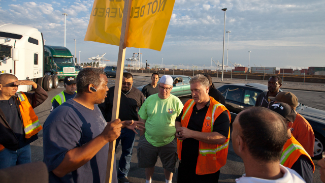 Truck Driver J.R. Coleman talks (left, holding sign) with Michael Villeggiantes, the president of the Local 10 Longshoreman's Union. (Deborah Svoboda / KQED)