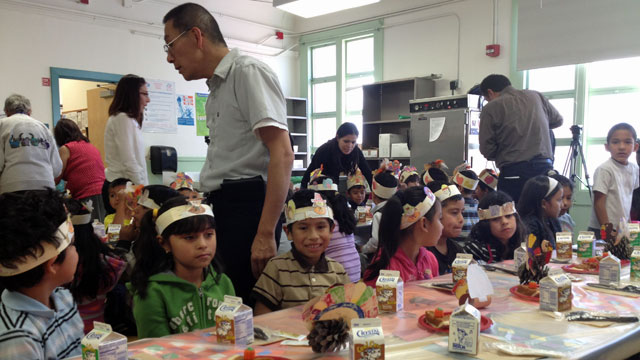 First grade teacher Mario Chang tries to keep his students quiet as they wait for the rest of the school to assemble for a Thanksgiving meal.