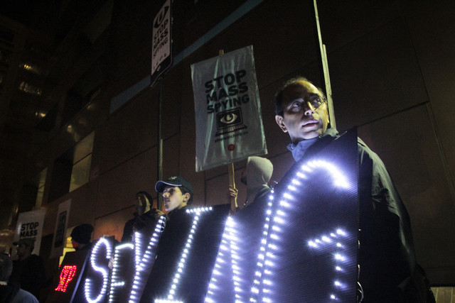 "At Tuesday's anti-surveillance protest, the Bay Area Light Brigade held signs reading ""stop spying"" and ""revolt."" (Jeremy Raff/KQED)"