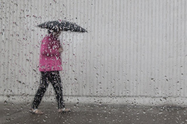 A pedestrian in downtown Oakland during storm earlier this week. (Mark Andrew Boyer/KQED)
