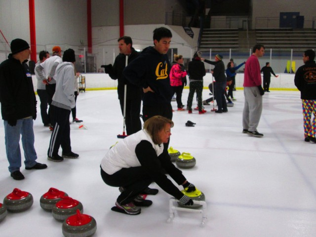 Bay Area Curling Club instructor Joseph Tang shows aspiring curler Nancy Carruth of San Francisco the basics at the Oakland Ice Center. (Nina Thorsen/KQED)