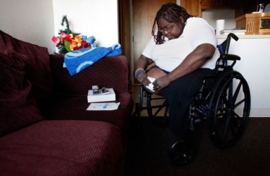 Juanita Hasnat, 47, cleans a wound on her leg in her Nevin Plaza apartment. Hasnat, whose legs were amputated after she contracted the flesh-eating bacteria MRSA, gave herself sponge baths out of her bathroom sink for months because her bathtub didn't have a safety bar. (Lacy Atkins/San Francisco Chronicle)
