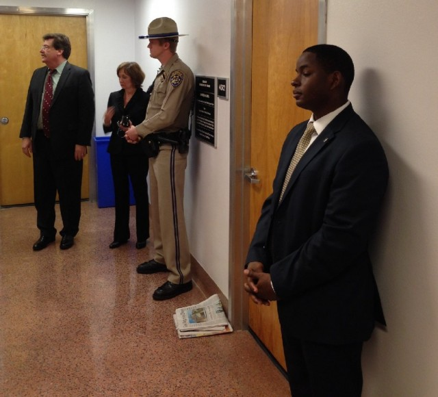 A California Highway Patrol officer and other officials outside Sen. Leland Yee's Sacramento office Wednesday. (Scott Detrow/KQED)