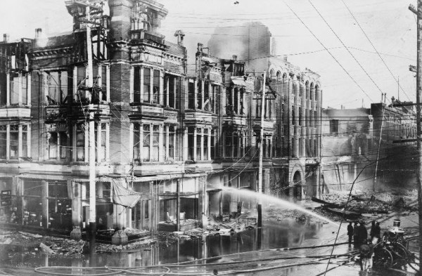 A fire truck sprays water on a block of burned buildings, June 8, 1906 (Library of Congress).