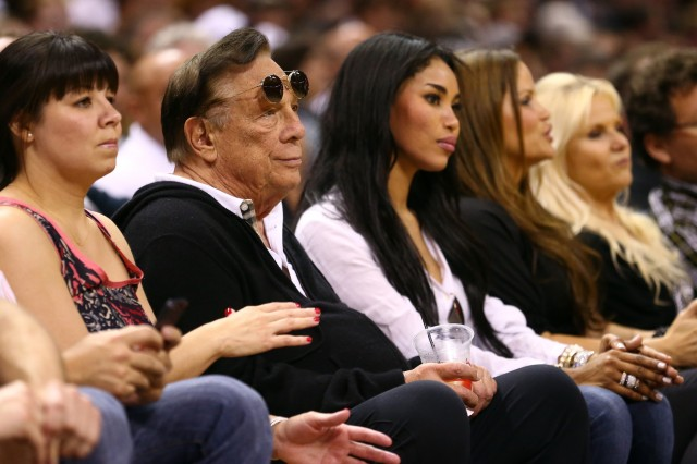 In happier times, Donald Sterling and V. Stiviano watch a basketball game together in May 2013 in San Antonio. (Ronald Martinez/Getty Images)
