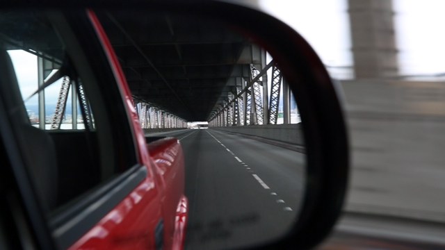 A rearview mirror reflects the apocalyptic scene driving onto the old Bay Bridge. (Adam Grossberg/KQED)