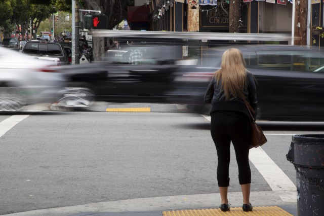 A pedestrian waits to cross South Van Ness Avenue at 24th Street in the Mission. (Mark Andrew Boyer/KQED)
