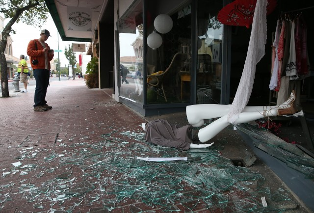 A mannequin lies in broken glass in front of a damaged building. (Justin Sullivan/Getty Images)