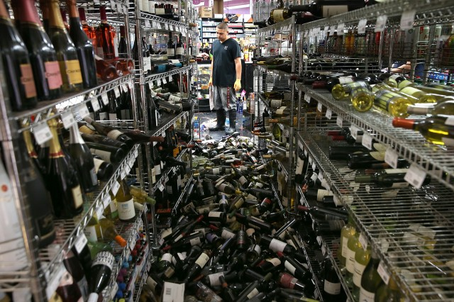 A worker looks at a pile of wine bottles that were thrown from the shelves at Van's Liquors. (Justin Sullivan/Getty Images)