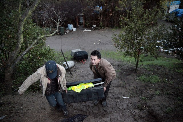 Jose Alcala, right, removes his belongings after living at The Jungle for two years. Rain and mud has complicated the move for many residents. (James Tensuan/KQED)