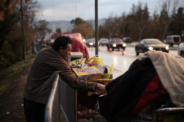 Residents dragged their belongings to the side of the road. Some had friends to pick them up. Others left on foot. (James Tensuan/KQED)