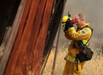 A Marin County firefighter takes a break amid 100-degree temperatures near the Lake County town of Lower Lake.