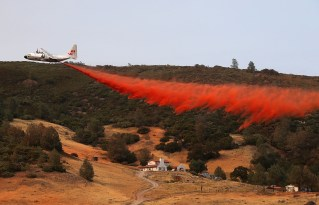 An air tanker drops fire retardant in an attempt to save a house during the battle to contain the Rocky Fire on Friday.