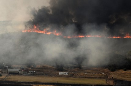 A wall of flames crests a ridge above a ranch southeast of Clear Lake on Thursday.