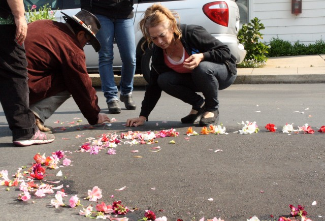 Family members and supporters of Yanira Serrano-Garcia spread flowers around the spot where she was killed near Half Moon Bay. (Alex Emslie/KQED)
