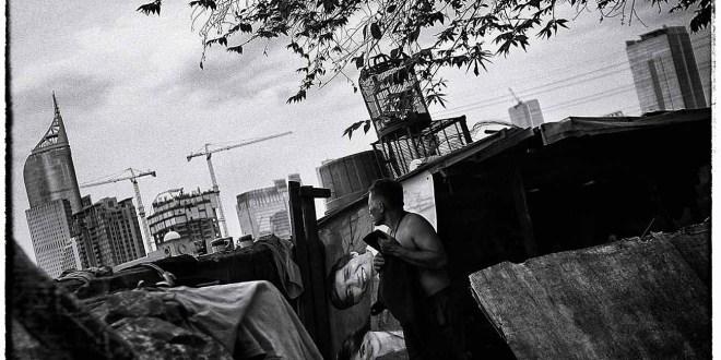 Warga melihat deretan gedung perkantoran dari pemukimannya yang berdiri di kawasan Banjir Kanal Barat, jakarta