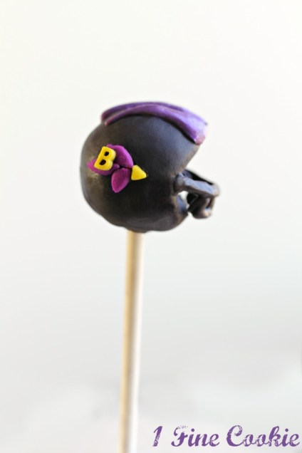 Cut a triangle out of your cake balls, 1 fine cookie, football cake pops, football helmet, football helmet cake pops, football, football cake, football recipes, nfl recipes, football party ideas, football dessert table, nfl dessert table, dessert table, recipes, how to, diy, nfl cake pops, baltimore ravens, baltimore ravens cake pops, ravens cake pops, ravens, 49ers, san fransisco 49ers, san fransisco 49ers cake pops, 49ers cake pops, cake, pops, how to make cake pops, football cake pops, football helmet cake pops, Bears, bears cake pops, chicago bears cake pops, Bengals, bengals cake pops, cincinatti cake pops, cincinatti bengals, cincinatti bengals cake pops, Bills, buffalo bills, bills cake pops, buffalo bills cake pops, Broncos, broncos cake pops, denver broncos cake pops, denver cake pops, denver, Browns, browns cake pops, cleveland, cleveland browns, cleveland cake pops, bfl cake pops, cleveland browns cake pops, Bucaneers, bucaneers cake pops, tampa bay bucaneers, tampa bay bucaneers cake pops, tampa bay cake pops, Cardinals, cardinals cake pops, arizona cardinals, arizona cardinals cake pops, arizona cake pops, Chargers, chargers cake pops, san diego chargers, san diego chargers cake pops, Cheifs, chiefs cake pops, kansas city chiefs cake pops, kansas city cake pops, kansas city cake pops, Colts, Indianapolis colts, colts cake pops, indianapolis colts cake pops, indianapolis cake pops, Cowboys, cowboys cake pops, dallas cake pops, dallas, dallas cowboys cake pops, Dolphins, miami dolphins, dolphins cake pops, miami dolphins cake pops, miami cake pops, Philadelphia cake pops, philadelphia eagles cake pops, Eagles cake pops, Falcons, falcons cake pops, atlanta cake pops, atlanta falcons, atlanta falcons cake pops, Giants, giants cake pops, ny cake pops, ny giants, ny giants cake pops, Jaguars cake pops, jaguars, jacksonville jaguars, jacksonville jaguars cake pops, jaguars cake pops, Jets, ny jets, jets cake pops, ny jets cake pops, Lions, lions cake pops, det