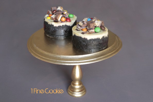 Everything but the Kitchen Sink Candy Cheesecake by 1 Fine Cookie, Chocolate Candy Filled Cheesecake by 1 Fine Cookie, &M's, Snickers, Twix, Reese's Pieces, brownie, bits, chunks, chocolate covered pretzels, Kit Kats, Reese's, peanut butter cups, Oreo cookie crust, chocolate, wafers, oreo, cookie, crust, peanut butter, cheesecake, colorful, leftover, halloween, recipe, what to do with, easy, foolproof, without sour cream, water, bath, classic, best, mini, springform, pan, gold, cake stand, food processor, mixer, hand mixer, birthday, best way to make, how do i,
