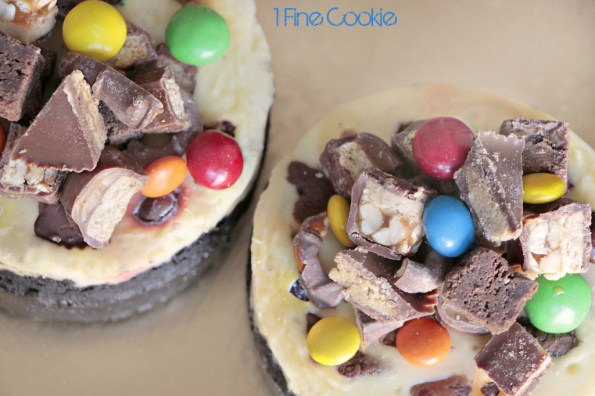 Filled Cheesecake Recipe by 1 Fine Cookie, Chocolate Candy Filled Cheesecake by 1 Fine Cookie, &M's, Snickers, Twix, Reese's Pieces, brownie, bits, chunks, chocolate covered pretzels, Kit Kats, Reese's, peanut butter cups, Oreo cookie crust, chocolate, wafers, oreo, cookie, crust, peanut butter, cheesecake, colorful, leftover, halloween, recipe, what to do with, easy, foolproof, without sour cream, water, bath, classic, best, mini, springform, pan, gold, cake stand, food processor, mixer, hand mixer, birthday, best way to make, how do i,