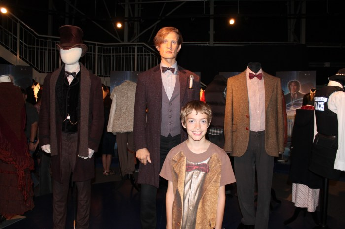 "The author's son wearing a Doctor Who ""costume"" shirt standing in front of a wax statue of Matt Smith"