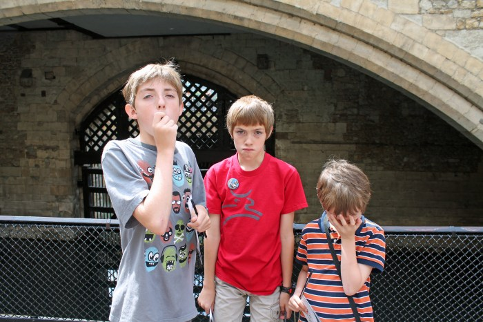 Photo of three kids making sad/scared faces in front of a castle drawbridge.