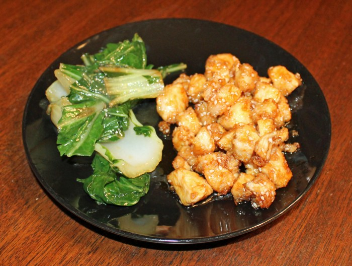 sesame chicken plated with a side of bok choy