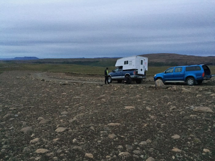 A camping trailer and a pickup truck on the side of a rocky dirt road, with no signs of habitation visible.
